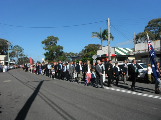 Ex-servicemen march along the main street of Wangi behind the piper & drummer